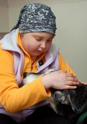 Jenny Boxer, 11-year-old girl with brain tumor, pets a dog