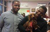 Two adopters with a small dog