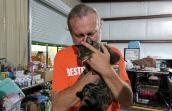Caregiver Mike Bzdewka cradles a cat after Hurricane Harvey
