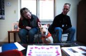 Jewel, the white shepherd and bull terrier mix dog, in between two people on a bench at the Best Friends Welcome Center