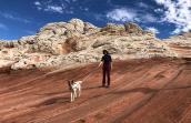 Volunteer Heather Harding with Sun the dog hiking on beautiful rock formations with blue sky and clouds behind them