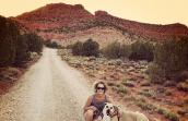 Jennifer Wesely taking a walk with Moqui the dog with red cliffs in the background