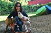 Smiling woman squatting down next to Diamond and Cookie the dogs