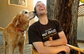 Man sitting on a chair and laughing while an elderly golden retriever sniffs his ear