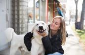 A smiling woman wearing a jacket hugging Ghost the dog, who is also smiling
