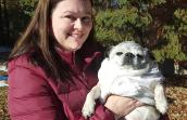 Brandy Rocchio holding Piper the pug while outside in front of some trees