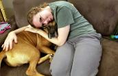 Woman leaning over on a couch and snuggling with Beaux the dog