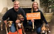 "Amber and Vince Krzys posing with Parker and their two other dogs holding a sign that says, ""Together we will Save Them All"""
