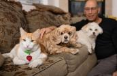 man with two dogs and one orange and white cat on couch