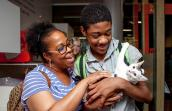 Woman and boy smiling and cradling a cat they're adopting