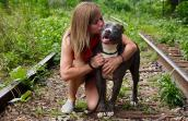 Volunteer Jamie Serratell kissing a gray and white pit bull terrier surrounded by some railroad tracks overgrown with greenery