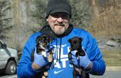 Man holding in cold weather clothing holding two small black and white puppies