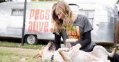 Woman sitting on the ground rubbing a dog's belly while in front of an Austin Pets Alive Airstream trailer