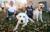 Eddie the great Pyrenees with his new adopted family, a man, woman and another dog