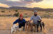 Patrick the dog posing with two other dogs and a couple with a sunset and hills behind them