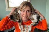 Woman wearing an orange sweatshirt with her cat wrapped around her neck on her shoulders while exercising