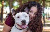 White and black pit-bull-type dog being hugged by the woman who adopted him who is smiling