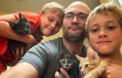 Man with two sons all holding foster kittens