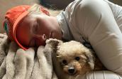 Woman wearing an orange hat lying down next to a rescued poodle