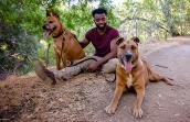 Brandon Alexander sitting on the ground next to Bear and Austin the dogs