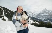 Woman holding a small dog with snow covered mountains in the background