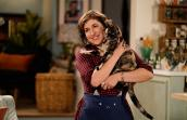 Mayim-Bialik holding a calico cat in her television series 'Call Me Kat'