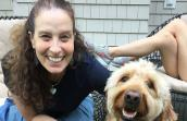 Volunteer Randi Schey posing next to a Labradoodle type dog