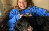 Alexandra Hinsley with a black dog in her lap