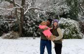 Caitlin and Max holding Jolene the dog in the snow