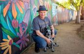 Man wearing a hat and Best Friends volunteer T-shirt with a heeler puppy in front of a colorfully painted wall