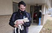 Man wearing a mask and holding a blond puppy cradled in his arms