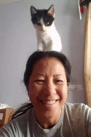 Volunteer Sophia Lim with a kitten on her head