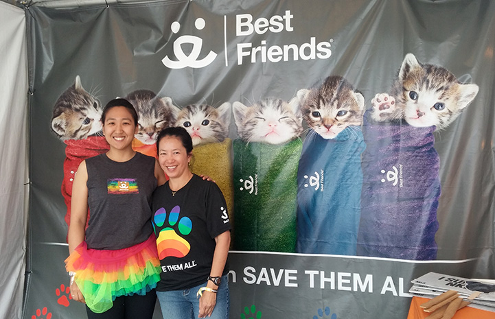 Volunteer Sophia Lim and another person standing by a Best Friends purritos sign