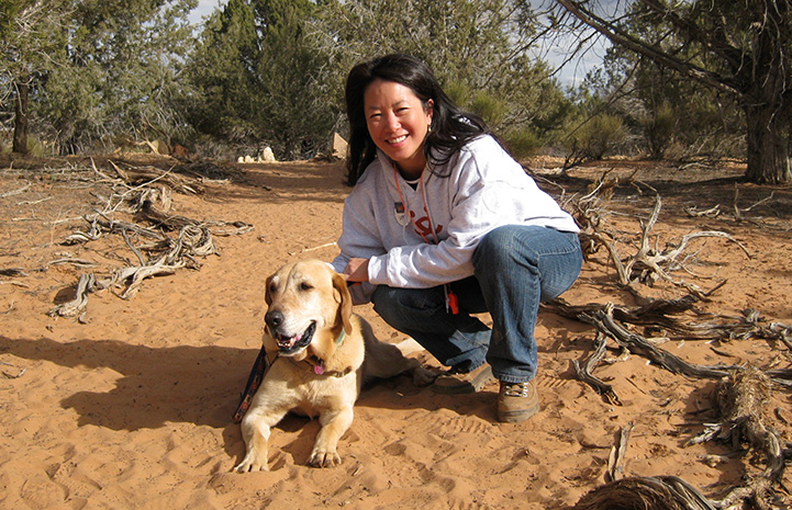 Volunteer Sophia Lim outside on a walk with a dog at Best Friends Animal Sanctuary