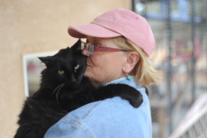 Patrick the black cat snuggling with caregiver Robin