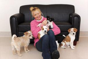Actress Charlotte Ross visits with some puppies