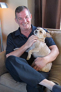 Ray holding Darby the dog who rescued him after his fall