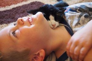 Dexter the super-senior cat snuggling with boy