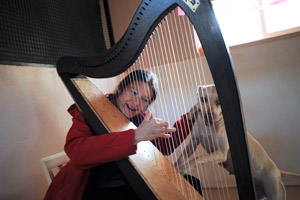 Ellen James plays the harp for Pearl the dog