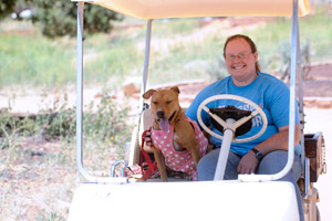 Fiesta the shy dog in her spotted pink dress and Alyssa riding in a golf cart