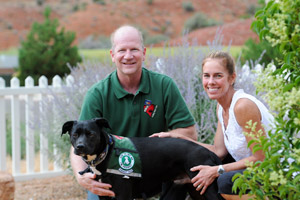 Therapy dog, a beautiful black Lab, with his adoptive mom and dad