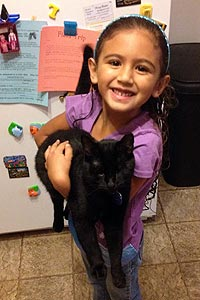 Little girl holding her adopted black cat