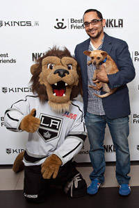Man holding the Chihuahua he adopted at the Los Angeles Kings game
