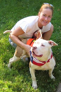 Woman and white and tan pitbull at an adoption event