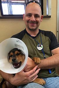 Daniel snuggling a puppy wearing a cone