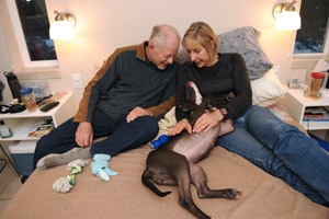 Melanie and John, a couple who volunteer together, enjoy time with Saydi the dog